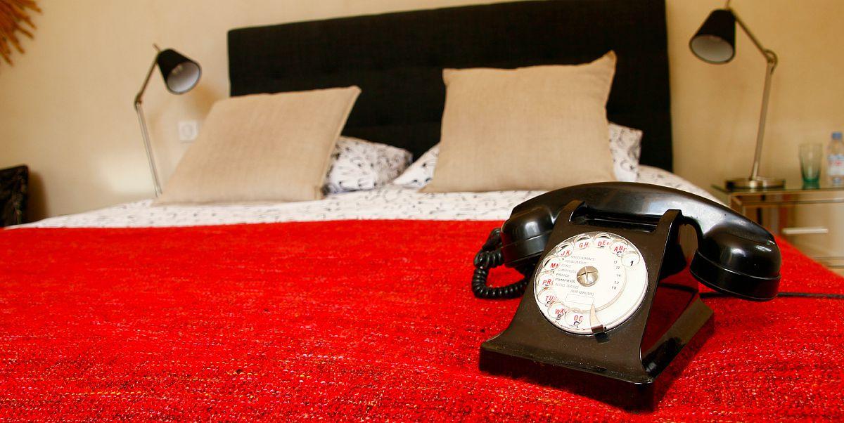 Téléphone vintage sur le lit de la chambre simple du Clos des Tilleuls de Verberie